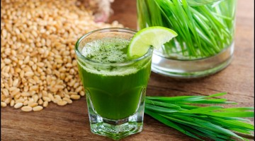 wheat grass juice with lemon on table