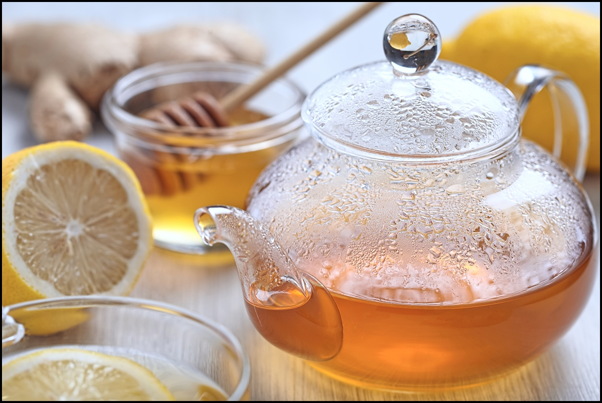 A pot of hot honey and lemon ginger tea on wooden table