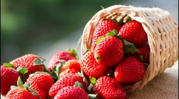 A small basket full of strawberries in natural background