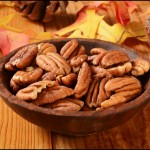 A wooden bowl of pecans on a table with pine cones