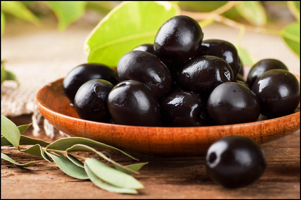 Black olives close up on wooden plate