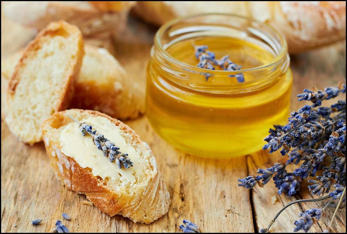 Bread with butter spread and jar of honey with lavender flowers