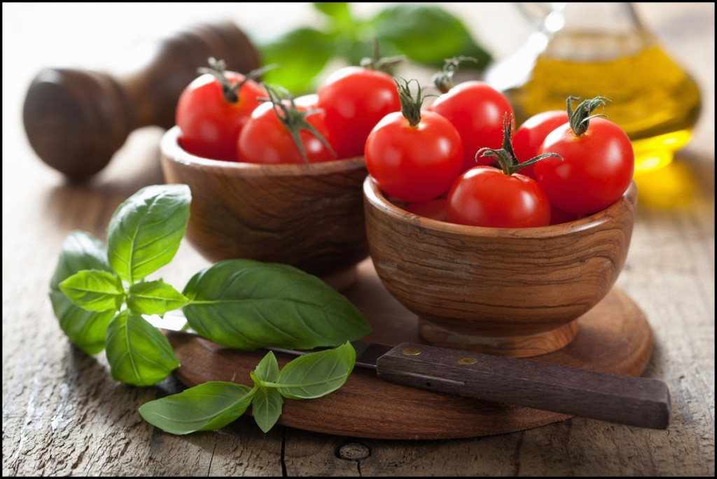 Cute little cherry tomatoes with basil leafs