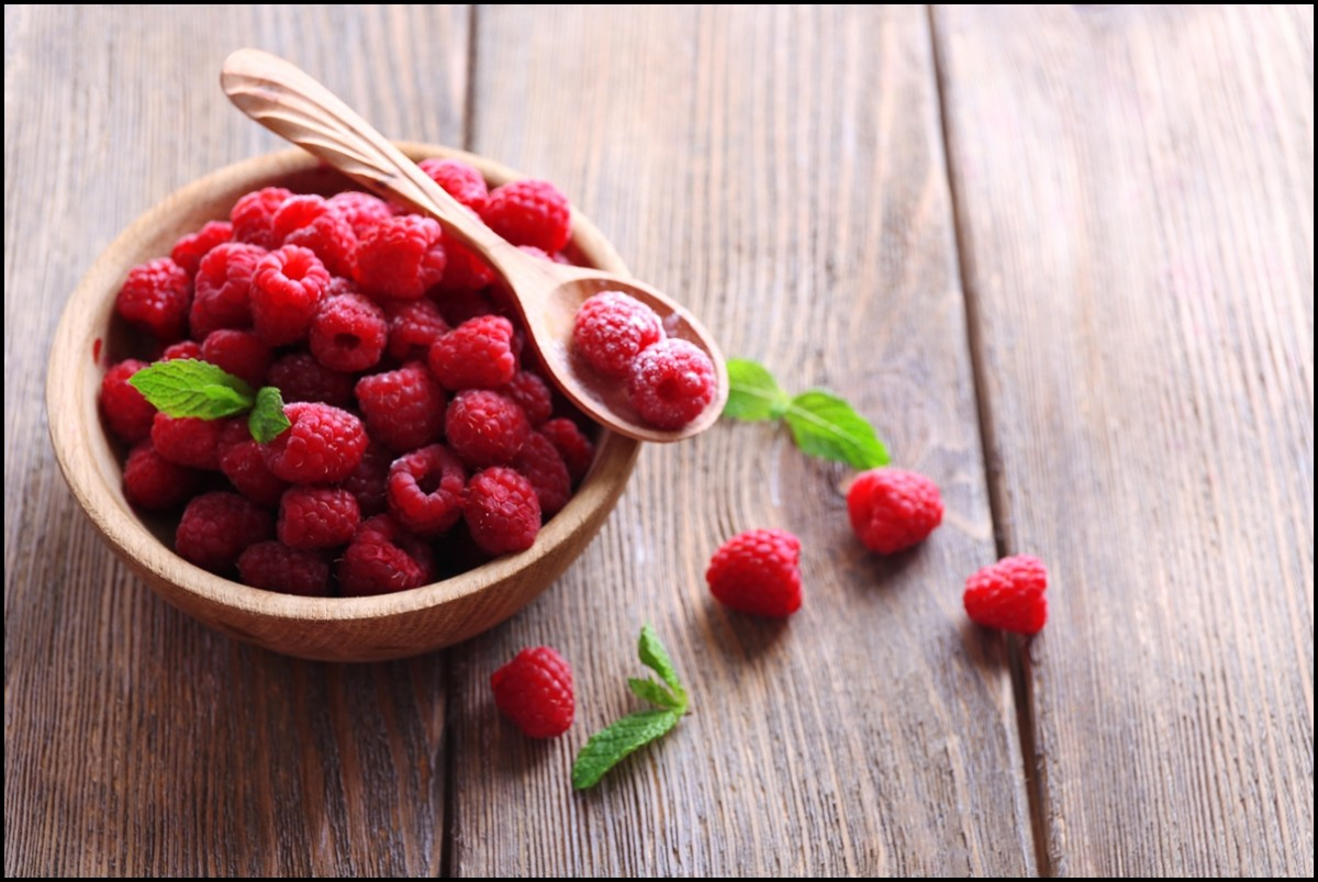 Delicious and healthy raspberries in a wooden bowl with mint leaf