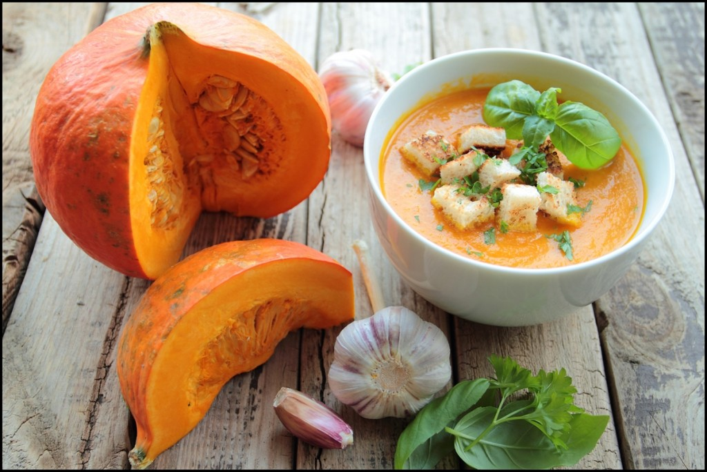 Delicious pumpkin soup with basil leafs and croutons