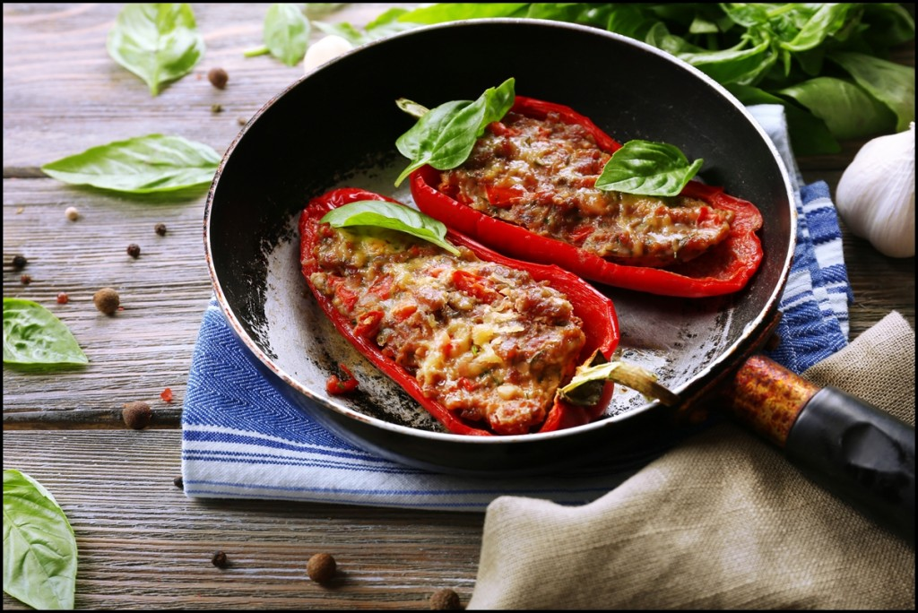 Delicious stuffed peppers in frying pan with leafs