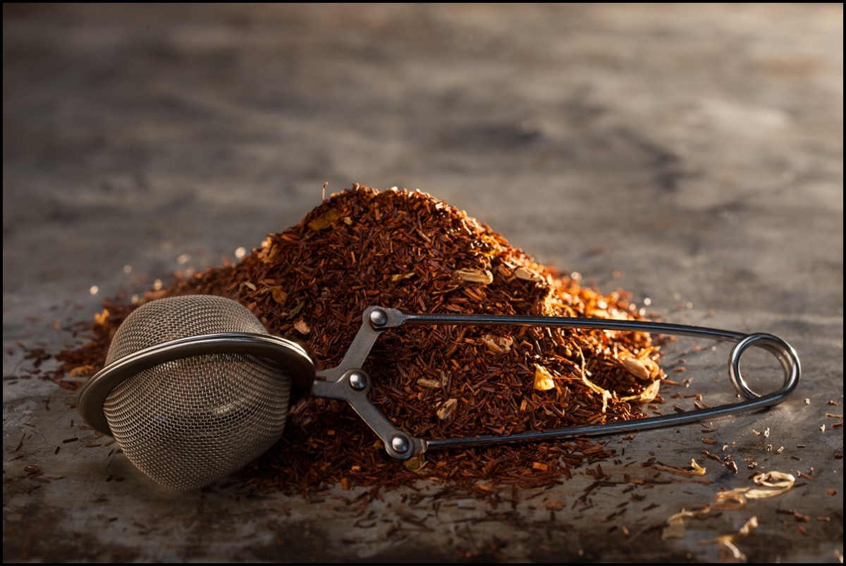 Dried Rooibos Tea and tea-strainer on a metal texture