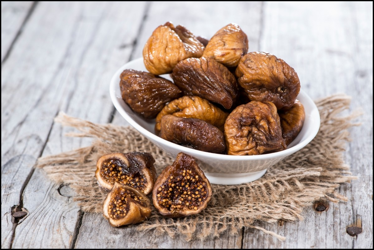 Dried figs in a bowl on wooden background