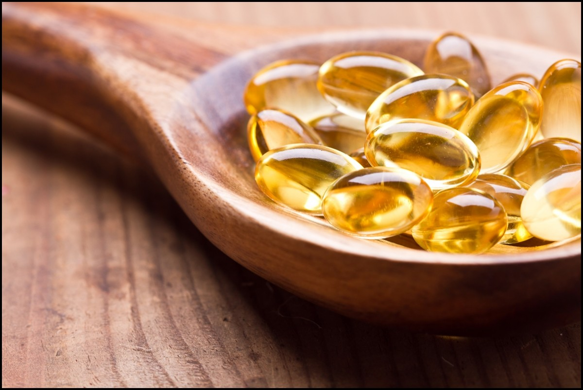 Fish oil in wooden spoon close up - Reasons to eat fish oil