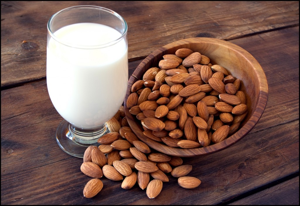Fresh almond milk in glass with almond nuts