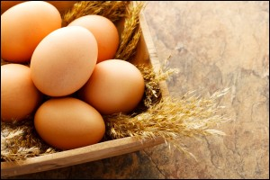 Fresh brown eggs in wooden square bowl