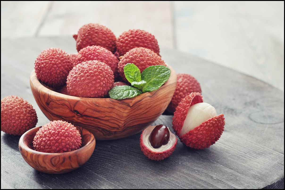 Fresh lychee in bowl on a wooden background