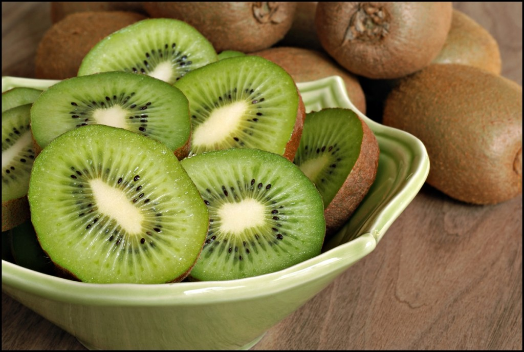 Freshly sliced kiwi fruit with whole kiwis