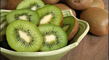 Freshly sliced kiwi fruit with whole kiwis