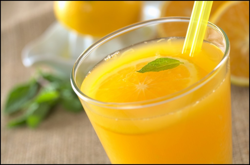 Freshly squeezed orange juice with drinking straws and orange slice, mint leaf on top of the juice