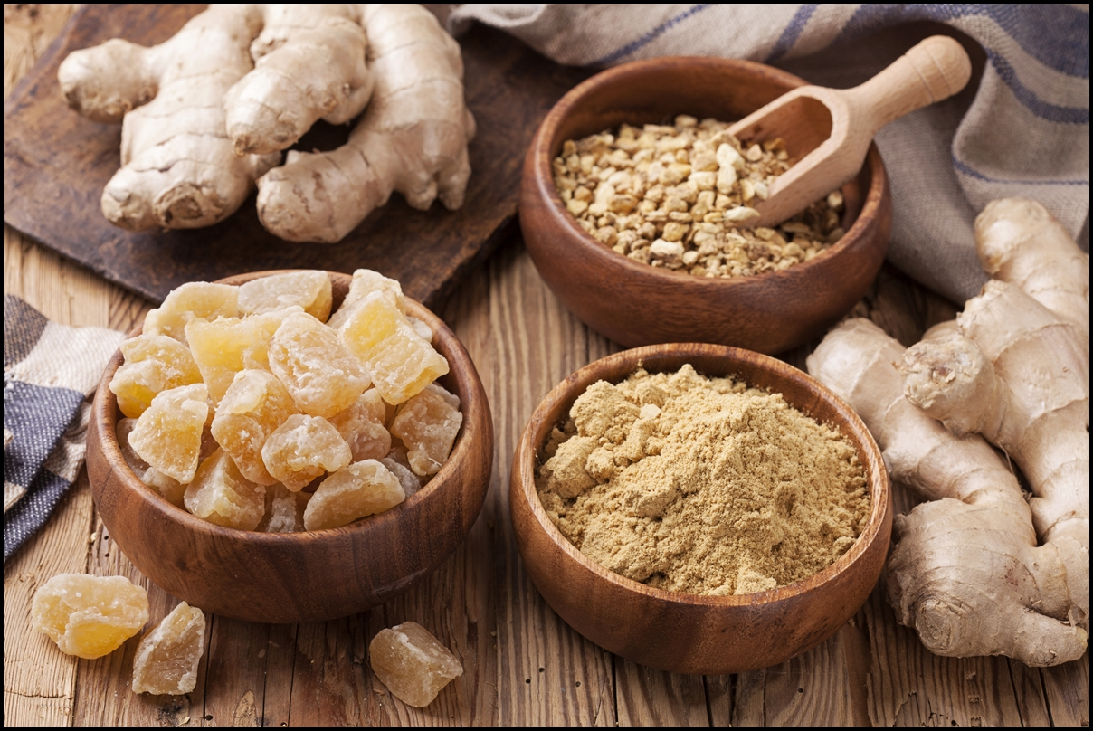 Ginger fresh root, ginger candy pieces and ginger spice on a wooden table