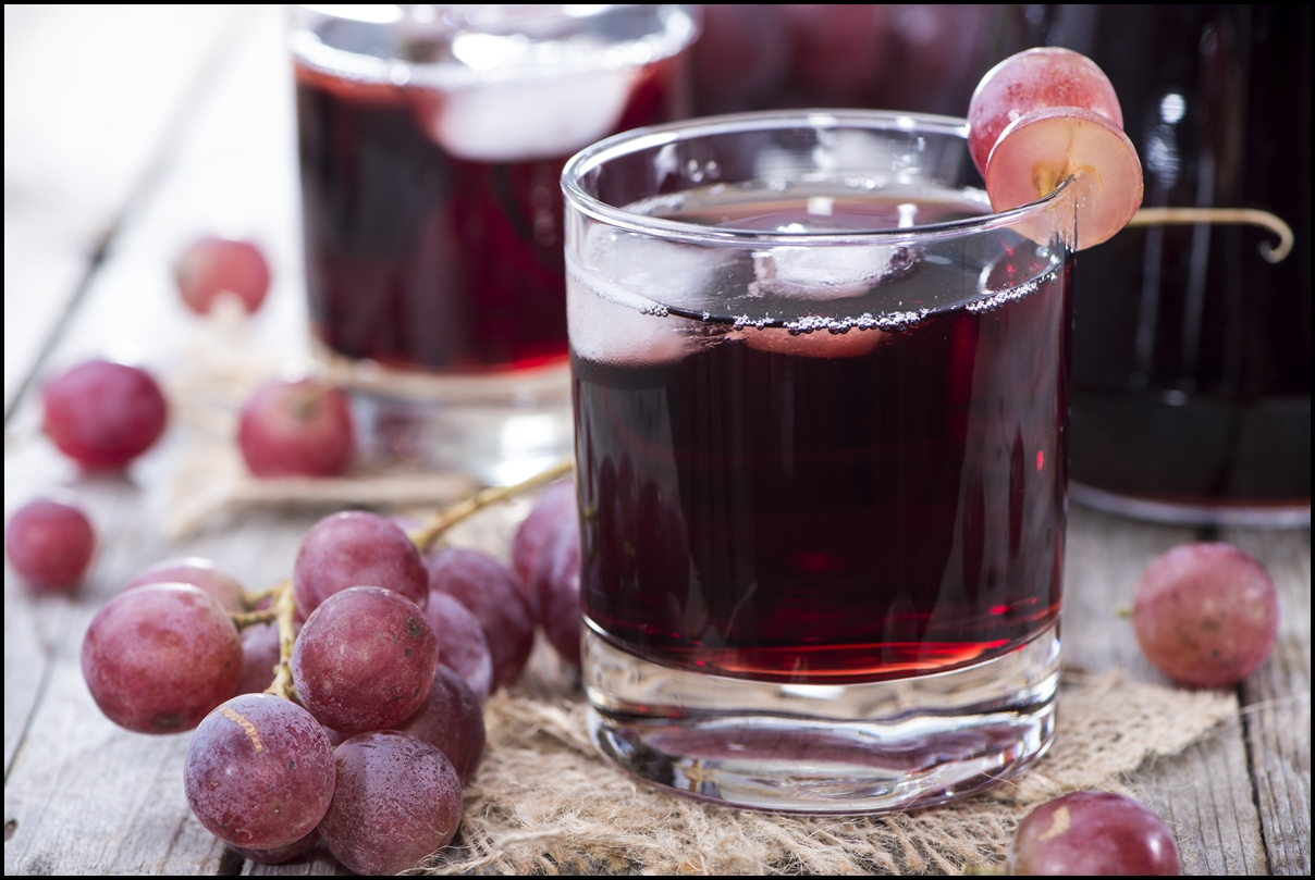 Glass filled with Ice Cubes and Delicious Red Grape Juice