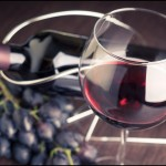 Glass of red wine with bottle and grapes.