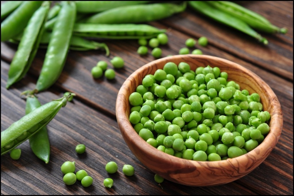 Green peas in wooden bowl