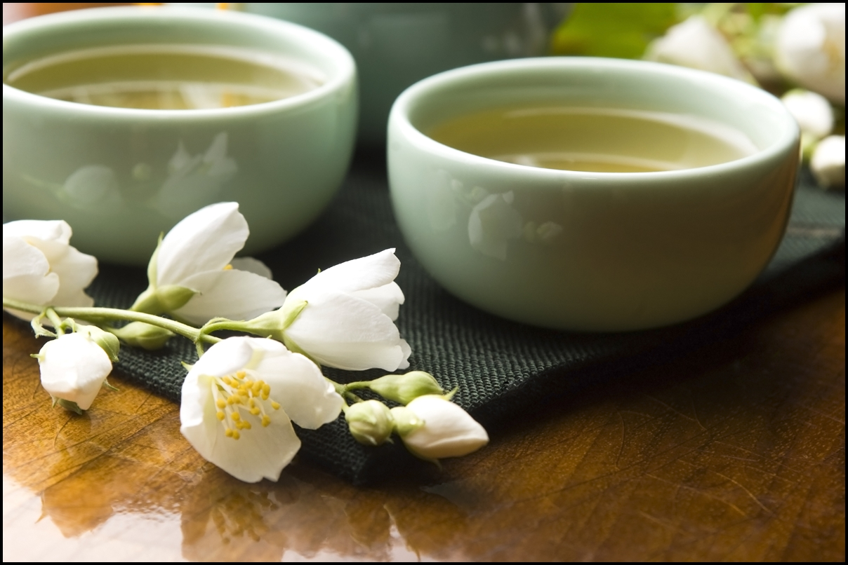 White tea with jasmine in cup and teapot on wooden table