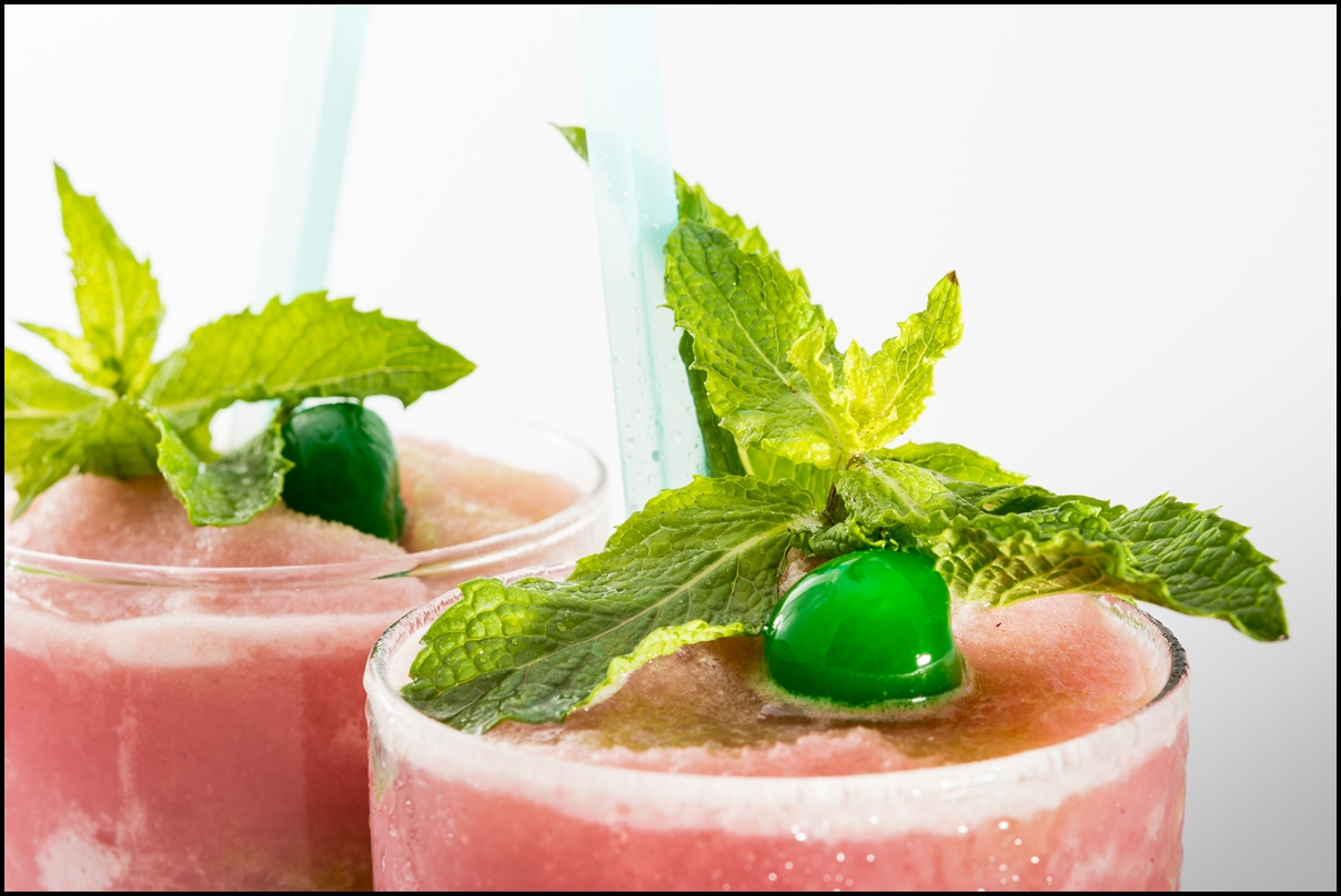 Guava smoothie garnished with green cherry and peppermint.