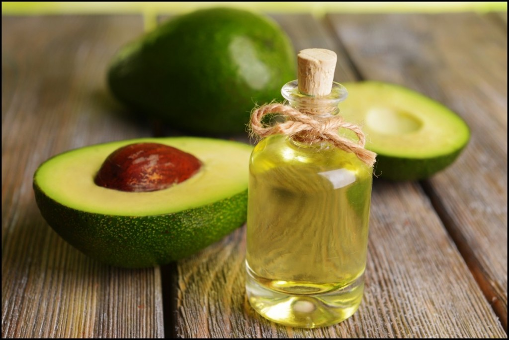 Halfed Avocado fruit and Avocado Oil on Wooden Table