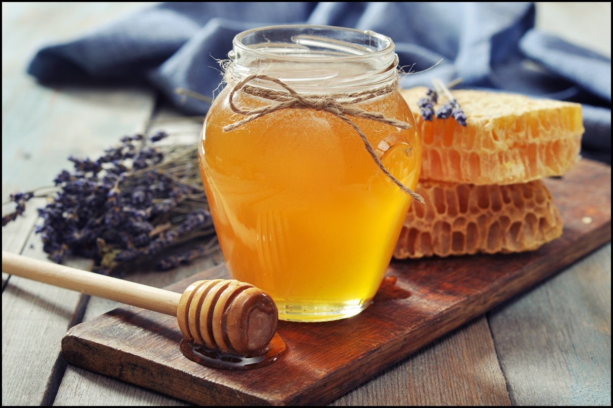 Honey in jar with honey dipper , honeycomb and lavender flowers on the side