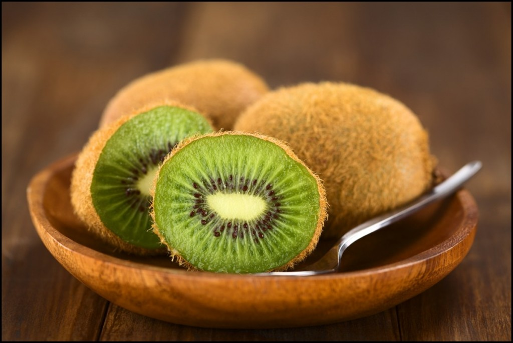 Kiwifruits on wooden plate close up
