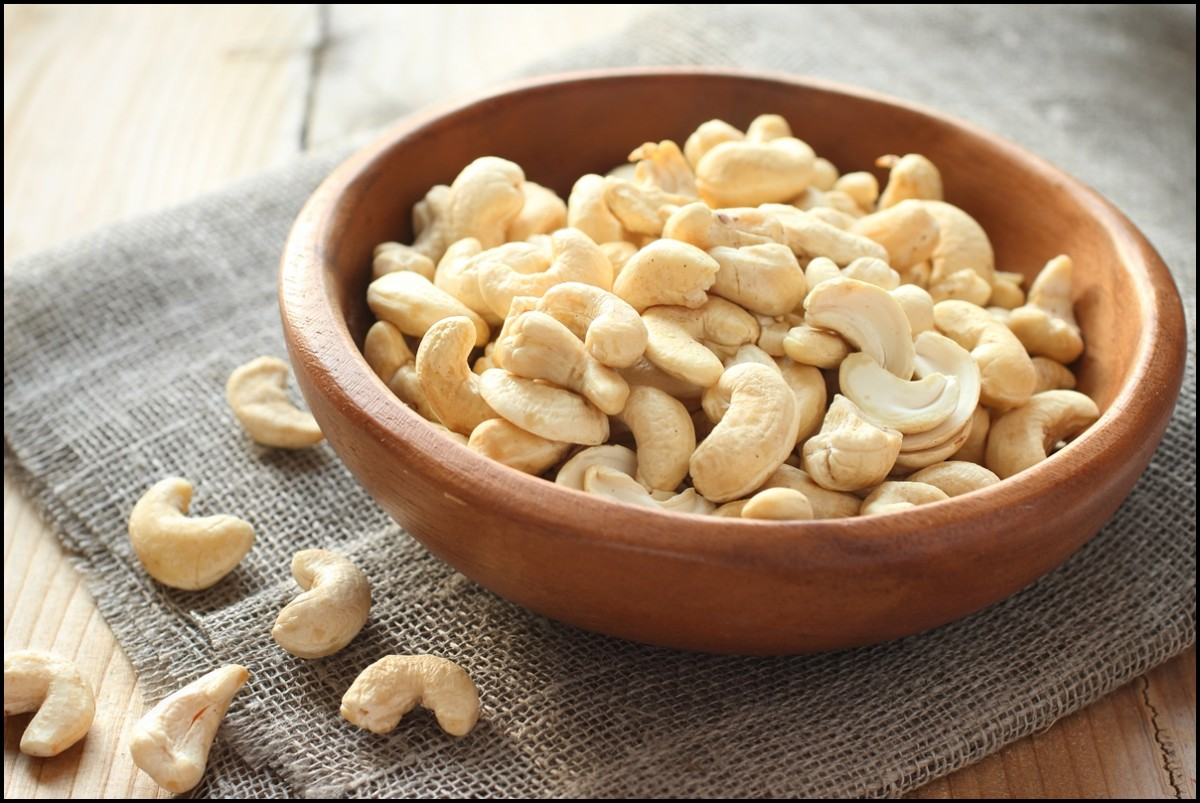 Raw cashews in wooden bowl on sackcloth
