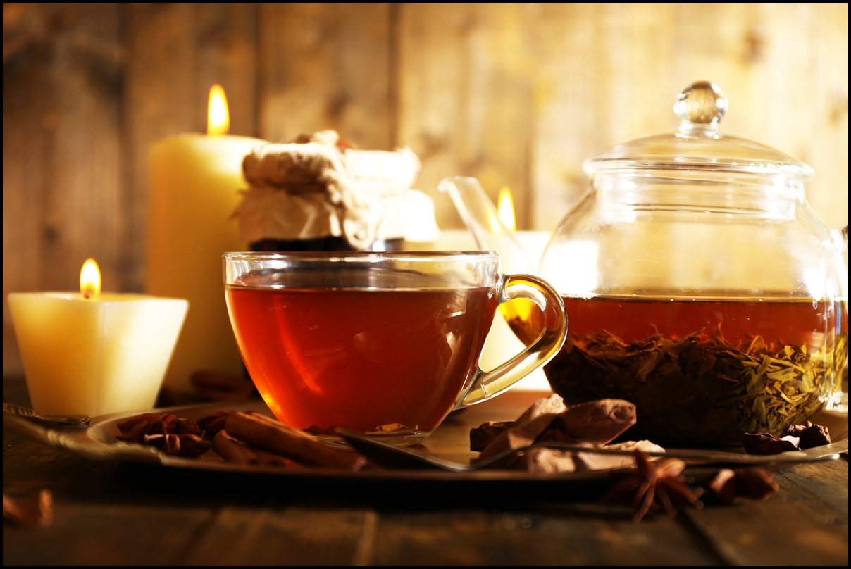 Red cinnamon tea in cup and teapot and candles on table