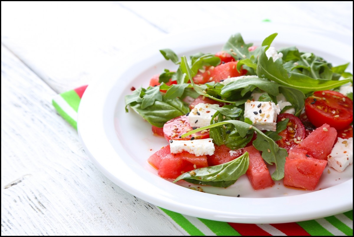 Salad with watermelon,tomatoes , feta, arugula and basil leaves on wooden background