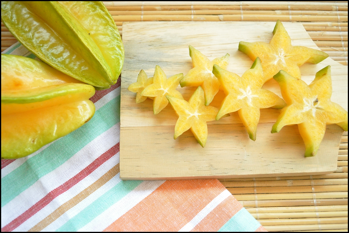 Top shot of starfruit on a wooden chopping board and stripe napkins