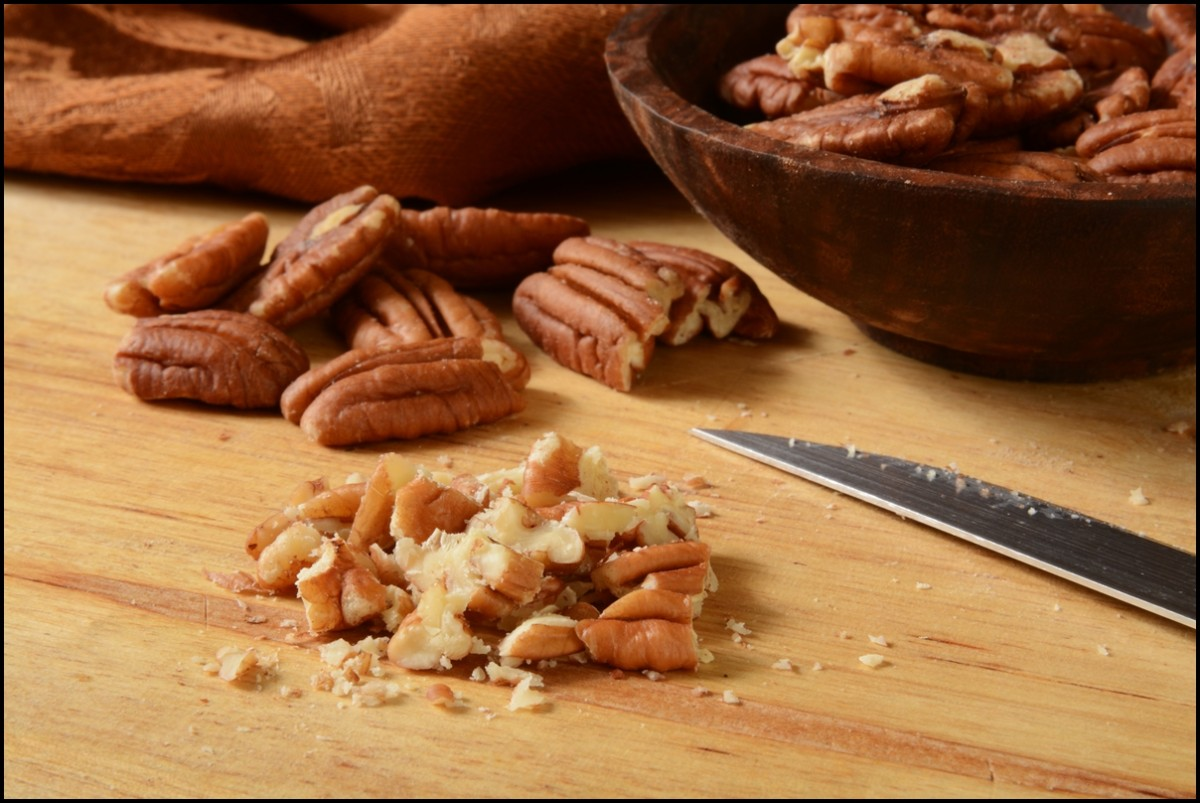 close up of chopped pecans on a cutting board