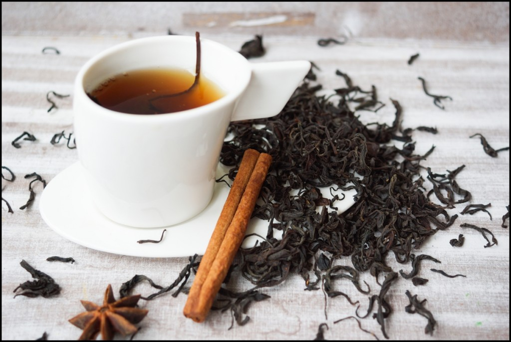 A cup of organic black tea and black tea leaves