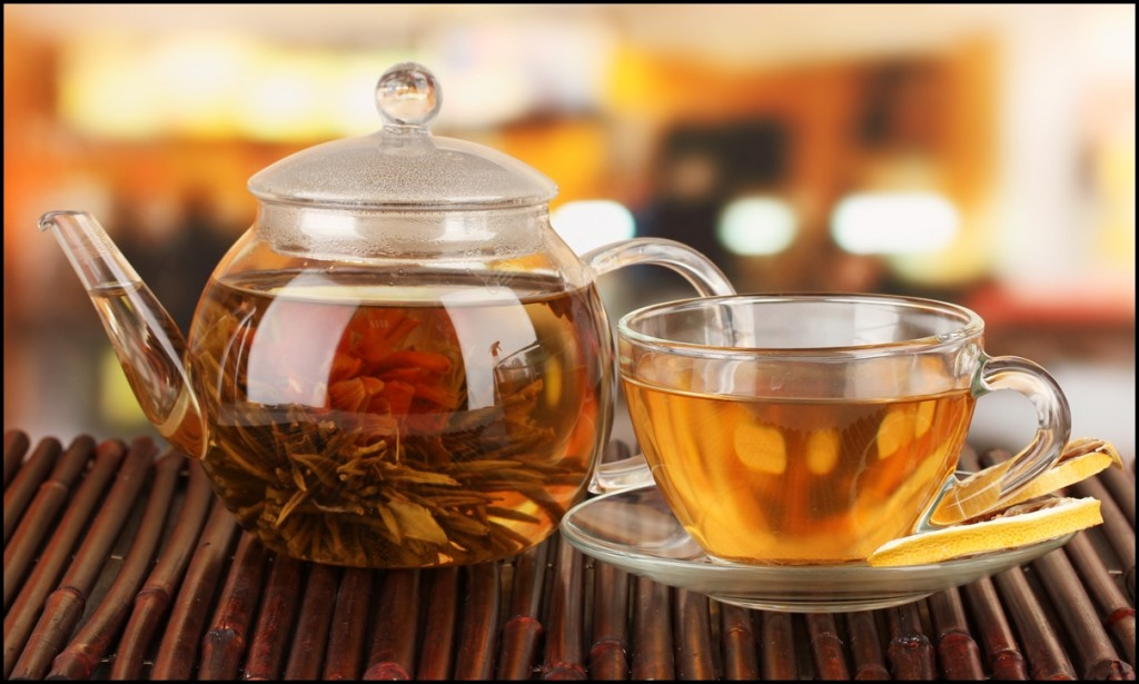 Exotic blooming green tea with flowers in glass teapot